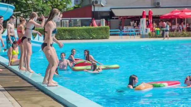 DOMZÁLIA, SZLOVÉNIA - 20. Június 2015 Az egyik a két lány ugrik egy felfújható levegő szőnyeg, majd beleesik a vízbe. A másik lány óvatosabb..
