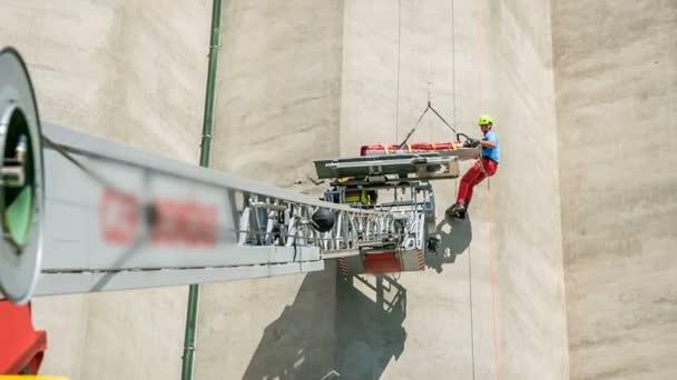 Egy mászó, aki segített megmenteni egy embert, úgy állítja be a hordágyat, hogy a sérült személy biztonságban lejusson..