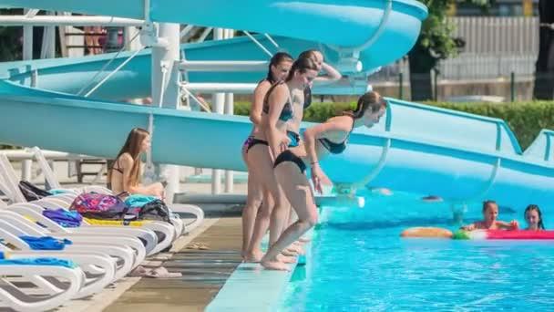 DOMZÁLIA, SZLOVÉNIA - 20. Június 2015 Öt tizenéves ugrik be a medencébe egyik a másik után.