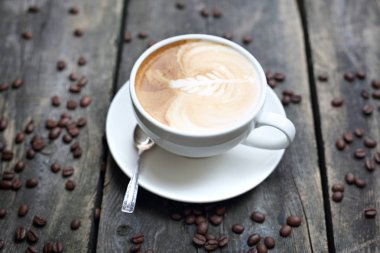 Cappuccino, cup of coffee with milk foam on a wooden background.