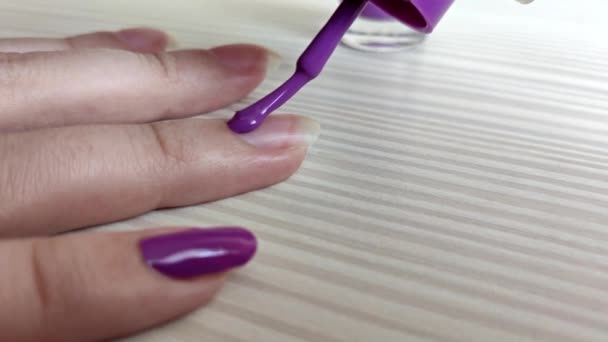 Žena maluje nehty fialovým lakem na nehty