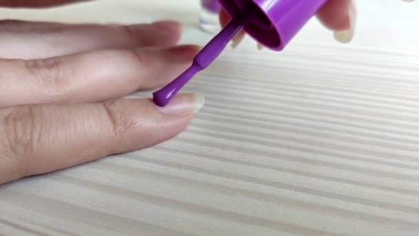 Frau lackiert Nägel mit violettem Nagellack