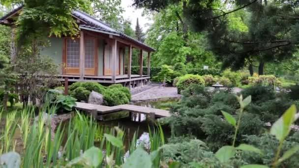 Japonský dřevěný dům stojí mlčky u jezírka mezi zelení