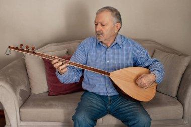An elderly man performing turkish string instrument baglama. String instruments concept with Turkish saz.
