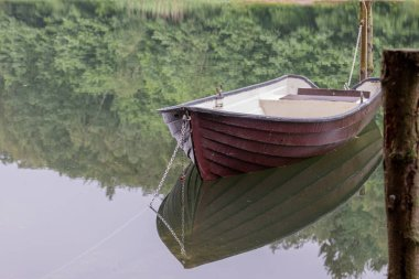 a chained rowing boat floats on a lake