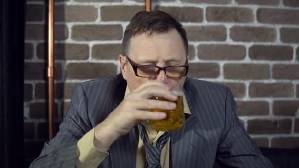 Businessman drinking alcohol indoors with brick wall.