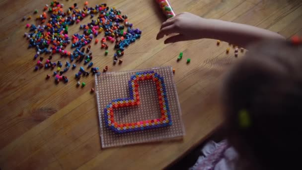 Little cute girl playing with colorful mosaic.