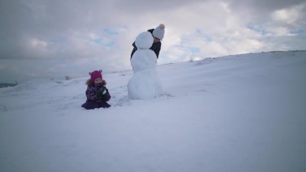 Žena a dítě spolu sochařství sněhuláka na kopci.