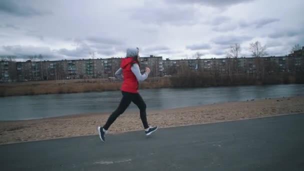 Mladá žena běží v parku v zamračený den.