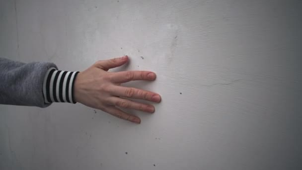 Female hand touch a plastered wall.