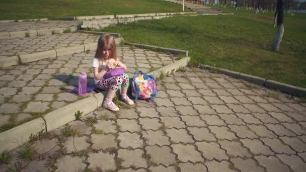 Blondýnka s obědem v parku za slunečného dne.