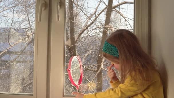 Little girl apply makeup for carnival on her face.