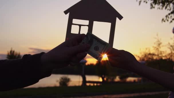 Nahaufnahme von Menschen übergeben Geld auf Hintergrund von Miniaturhaus.