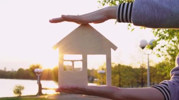 Közeli kezek tartsa a házat naplementekor.