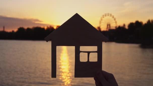 Těsné ruce drží dům při západu slunce.