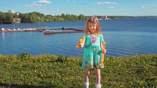 kleines blondes Mädchen bläst große Seifenblasen vor Meereskulisse auf.