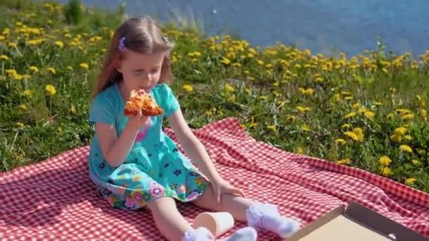Küçük sarışın kız sıcak bir günde deniz kıyısında pizza yiyor.