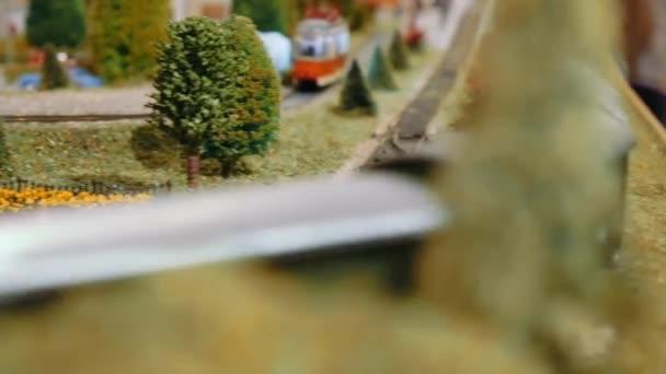 Modell-Güterzüge und Straßenbahn fahren vorbei, begegnen sich und kreuzen sich auf einem Diorama