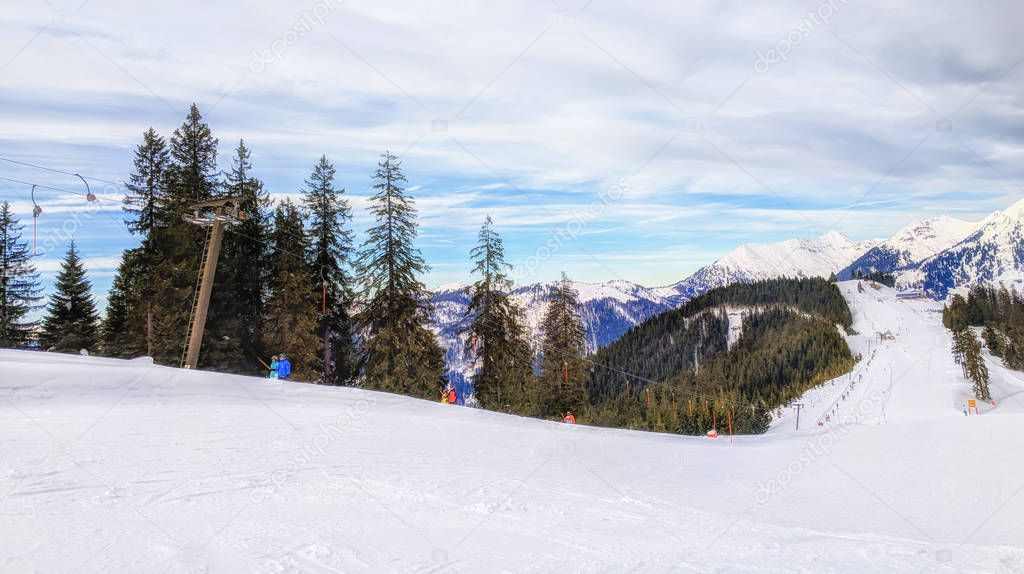 Unrecognizable skiers on beautiful ski slope in Alps