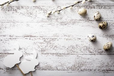 Easter, quail eggs, willow branches  and bunny on a wooden background
