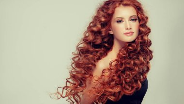 Beautiful model girl with red  curly hair  .Young woman with short wavy hairstyle