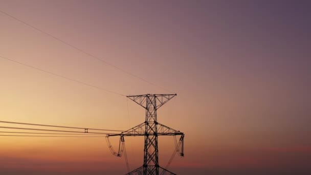 Aerial view drone shot. High voltage metal post. High-voltage towers in the forest with moving at sunset with twilight sky and clouds background. footage video b roll 4k.