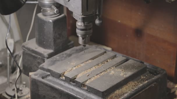 Drill press is being cleaned with a vacuum cleaner