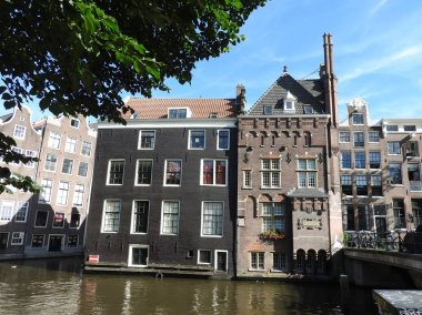 Facades and architecture of buildings in Amsterdam on a clear day.
