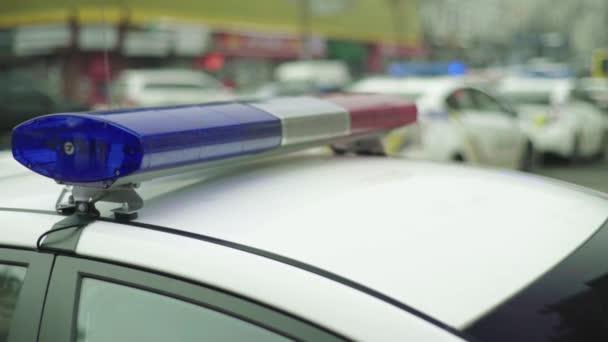 Policejní blikač blikající na střeše hlídkového vozu