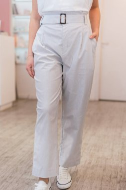 light light pants on the girl. young girl standing in fashionable linen trousers on a pink background in the store.