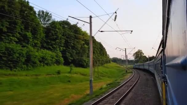 Výhled z vysokorychlostního vlaku na krásnou scenérii s kopci a lesem před západem slunce. Výhled z okna auta, autobusu, vlaku. Cesta vlakem za slunečného dne