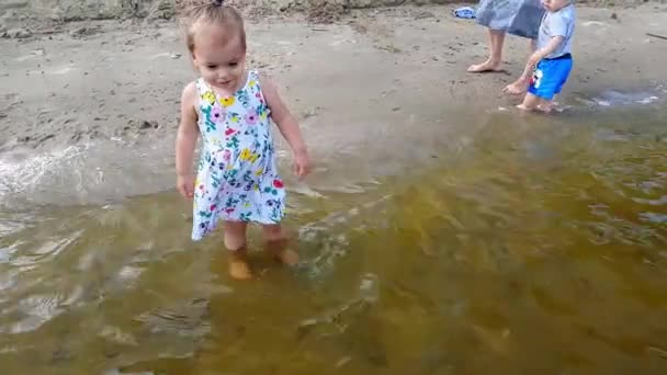 A little girl stands in the water near the shore in a flowered dress and is happy