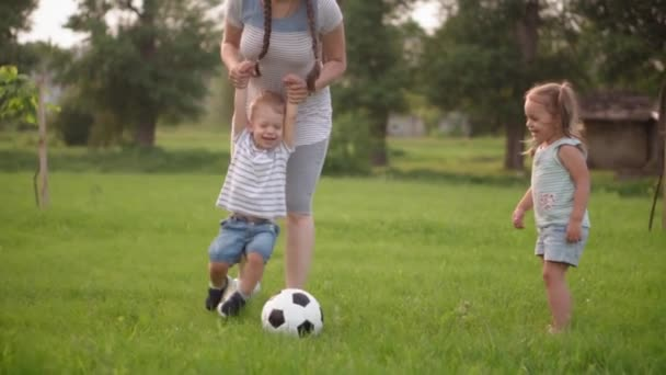 Childhood, games and entertainment, sports, physical culture, parks and open air concept - little kids boys and girls with mom play football with black and white ball on green lawn in park at sunset.