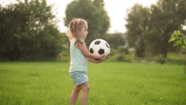Kindheit, Spiel und Unterhaltung, Sport, Körperkultur, Open-Air-Konzept - kleine Mädchen in kurzen Hosen und zwei Pferdeschwänzen spielen Fußball mit schwarz-weißem Ball auf hellgrünem Rasen im Park bei Sonnenuntergang