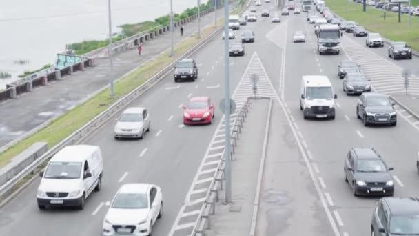 Kyjev, Ukrajina -18.05.2020: obecný plán letecké fotografie pohled na dálnici s mnoha osobními a nákladními automobily v blízkosti široké řeky Dněpru ve večerních hodinách. doprava, komunikace, infrastruktura, urbanizace koncepce