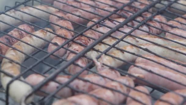 Kavárny a restaurace, vaření, piknik, orientální kuchyňská koncepce - detailní uzeniny na grilu navlečené na špejli, uzené a smažené na pražených uhlících. Venkovní pánské ruce připravuje k jídlu.