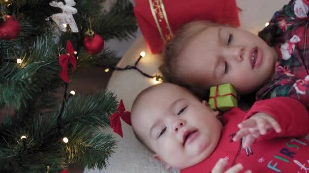 veselé Vánoce a šťastný nový rok, kojenec, dětství, dovolená koncept - close-up 6 měsíců staré novorozeně v Santa Claus klobouk a červené bodysuit s starší sestrou ležel na posteli s míčky v blízkosti vánoční strom.