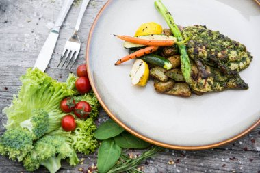 Chicken pesto salat with fresh vegetables on white plate