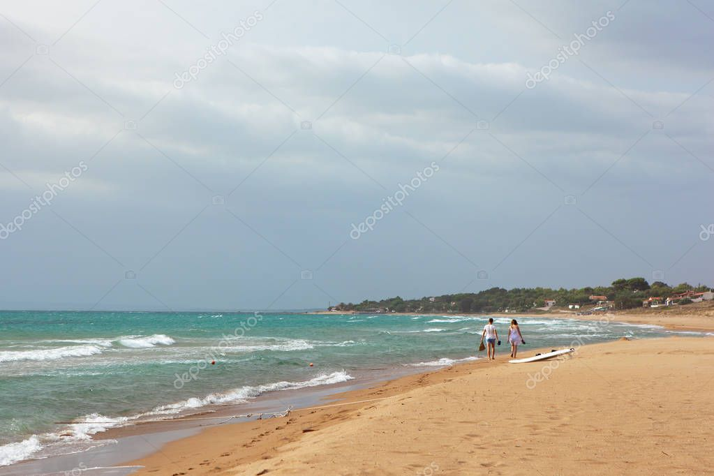 Summer sea view sandy beach, waves in sunny day. Sparkling waves lapping on the beach. Two teenagers walk along the shore. Travel and vacation concept. Overall plan. Copy space.