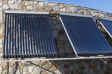 Solar water heating system installed on wall or roof of house. 3 panels of glass coaxial tubes with water to accumulate heat. Side view. Concept environmentally friendly and economical home heating.