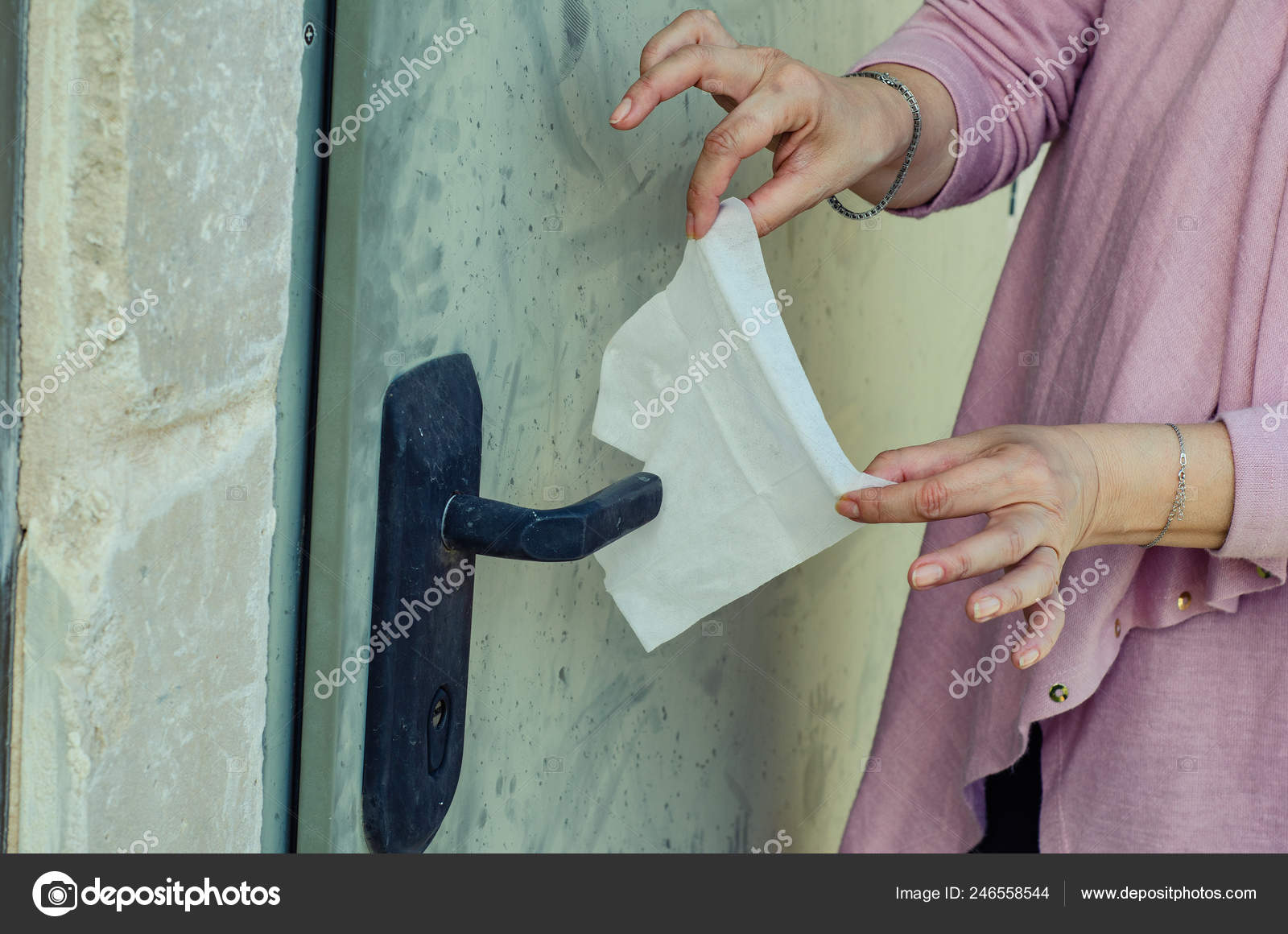 A woman with germophobia prepares a napkin to cover the handle of the entrance door.