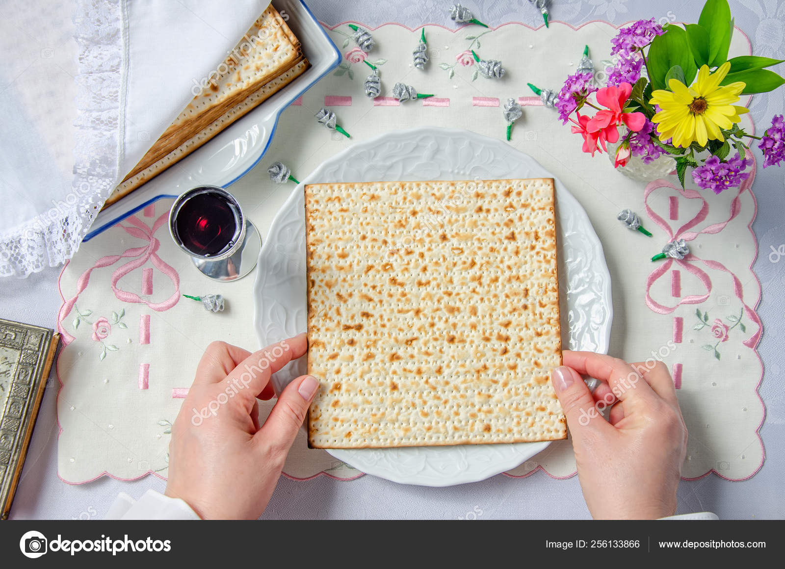 Hands had just pulled the matza out of the pack and put it on a white plate. The table is covered with a holiday tablecloth.