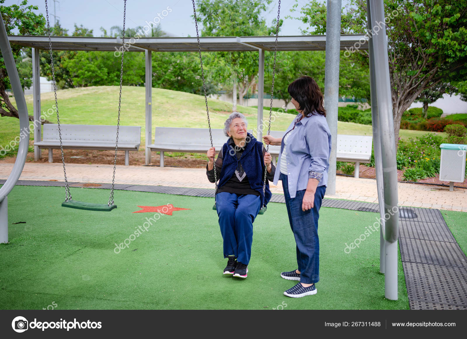 Elderly woman likes swinging during a daily walk in the park. Nearby is a female carer who helps her.