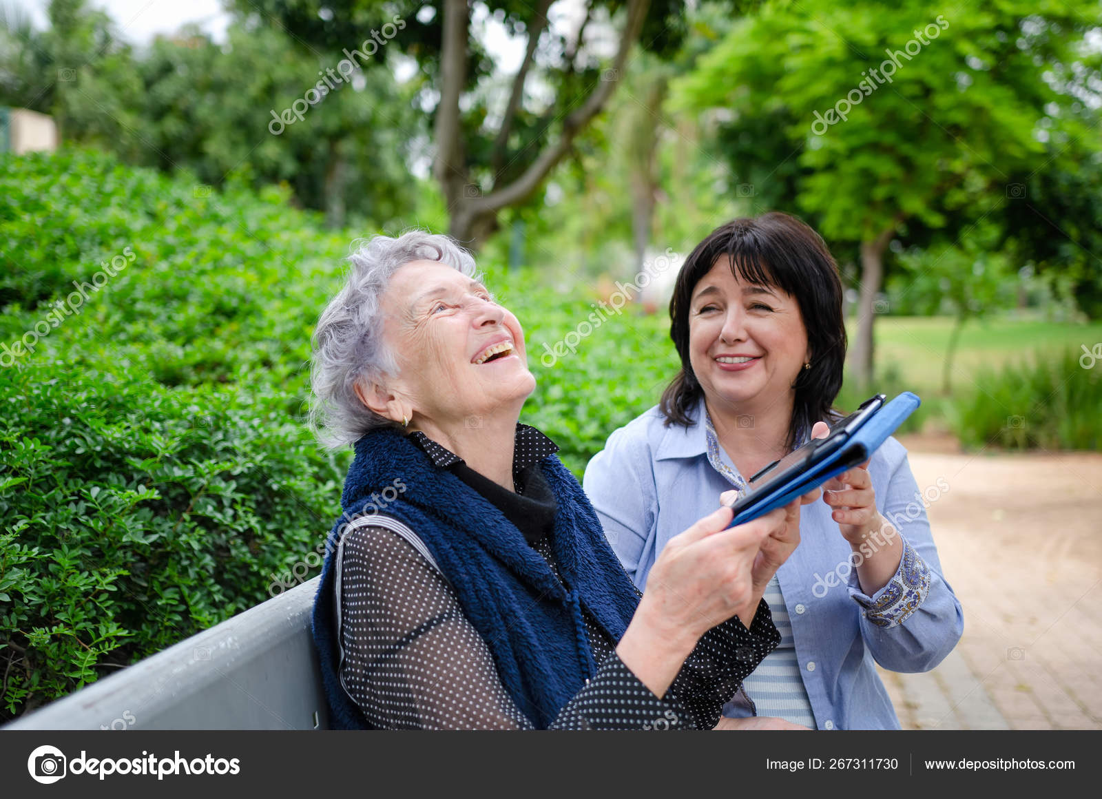 Female caregiver successfully teaches a senior woman to use a tablet sitting on a park bench