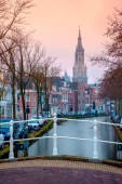 LEIDEN, NETHERLANDS - APRIL 5, 2018:Typical Dutch architecture on street with water channel in scenic town at sunset