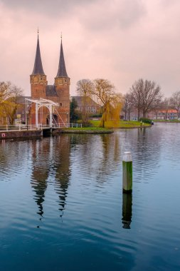 Evening view of the canal and the VVE Oostpoort de Delft. Dutch city in the spring at sunset. Holland, Netherlands.