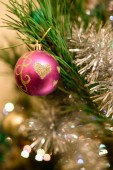 Pink ball Christmas ornament with hearts pattern on festive fir tree