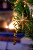 Fotografie Star-shaped bauble hanging on festive Christmas fir tree on fireplace background