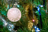 White ball Christmas ornament with snowflake pattern on fir tree branch