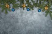 Ferienarrangement von Weihnachtstannenzweigen mit Kugeln und Sternenkugeln auf Grunge-Hintergrund